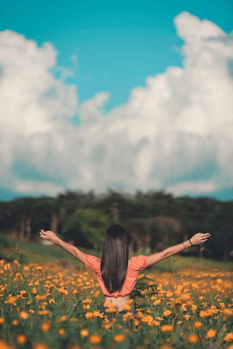 woman standing on flower field and raising her both hands