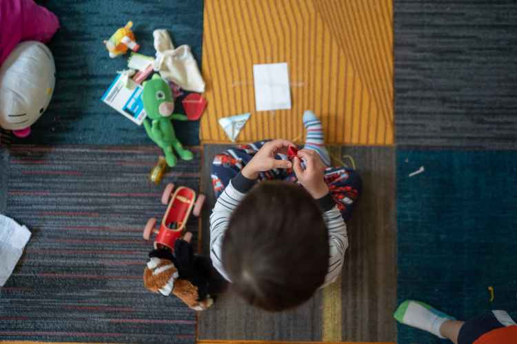 top view photography of toddler playing with toy